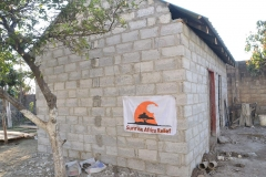 Side view of new toilet block with hanging Sunrise Africa Relief banner