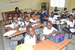 School children happily pose with their teacher in a classroom