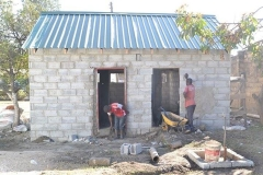 Local contractors working on the toilet block surrounded by building materials