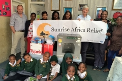 Robert and Paul hold Sunrise Africa Relief banner surrounded by IT donations and schoolchildren from Greenfield Community Primary in Johannesburg