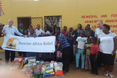 Robert and Paul outside Mponegele Ke Itirele with children and food donations