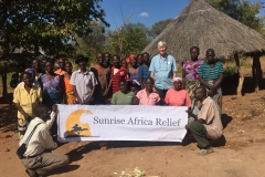 Locals and Robert with Sunrise Africa Relief banner