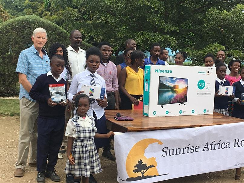 Trustee Robert Williamson and schoolchildren with new equipment