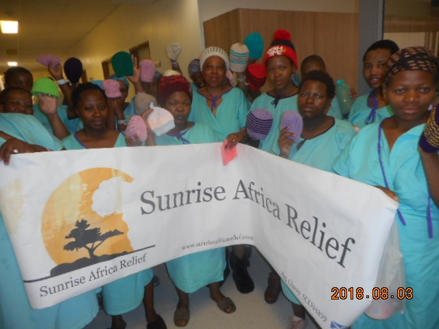 Patients at Queen Mamohato Memorial hospital hold the Sunrise Africa banner