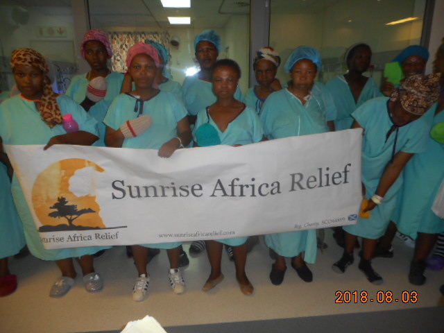 Patients hold the Sunrise Africa Relief banner