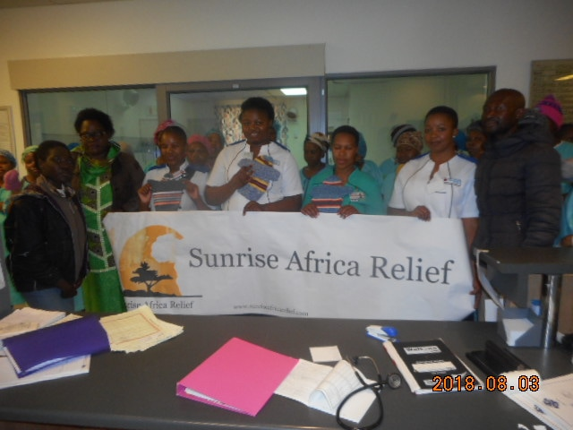 Staff and patients with charity banner
