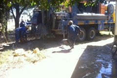 Employees from the drilling company clear the area beside the drilling vehicle