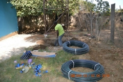 Contractor digs beside the borehole surrounded by tubing