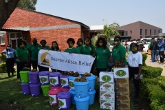 Staff with Sunrise Africa Relief banner and supplies