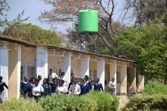 Large group of school children group outside the school, with new water tower in background