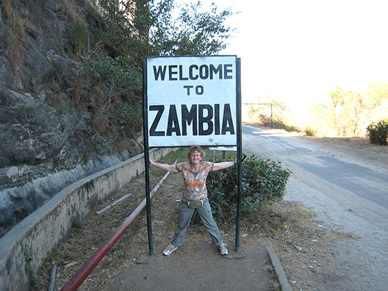 "The author beside a sign ""Welcome to Zambia"""