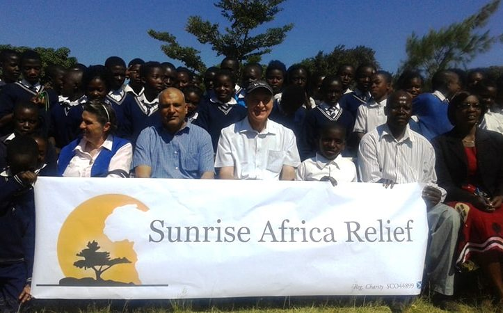 Trustees of Sunrise Africa Relief with charity banner and school children
