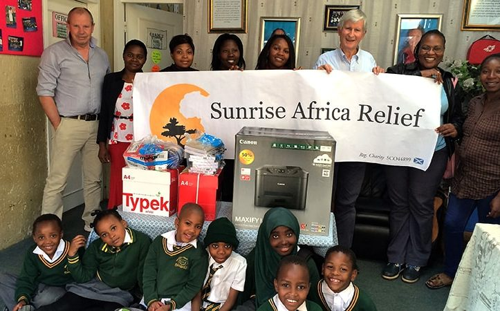 Sunrise Africa Relief with charity banner giving I.T. donations to Greenfield Community Primary School, Johannesburg